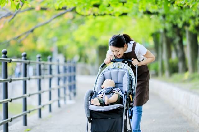 ベビーカーの赤ちゃんをあやすお母さん